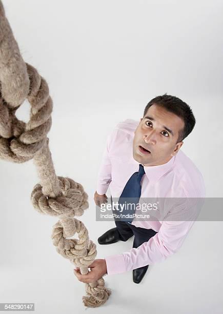 Businessman looking at rope