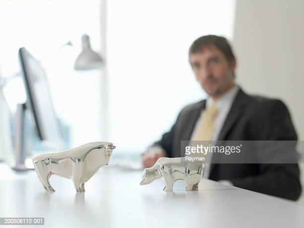 Businessman looking at silver model animals on desk