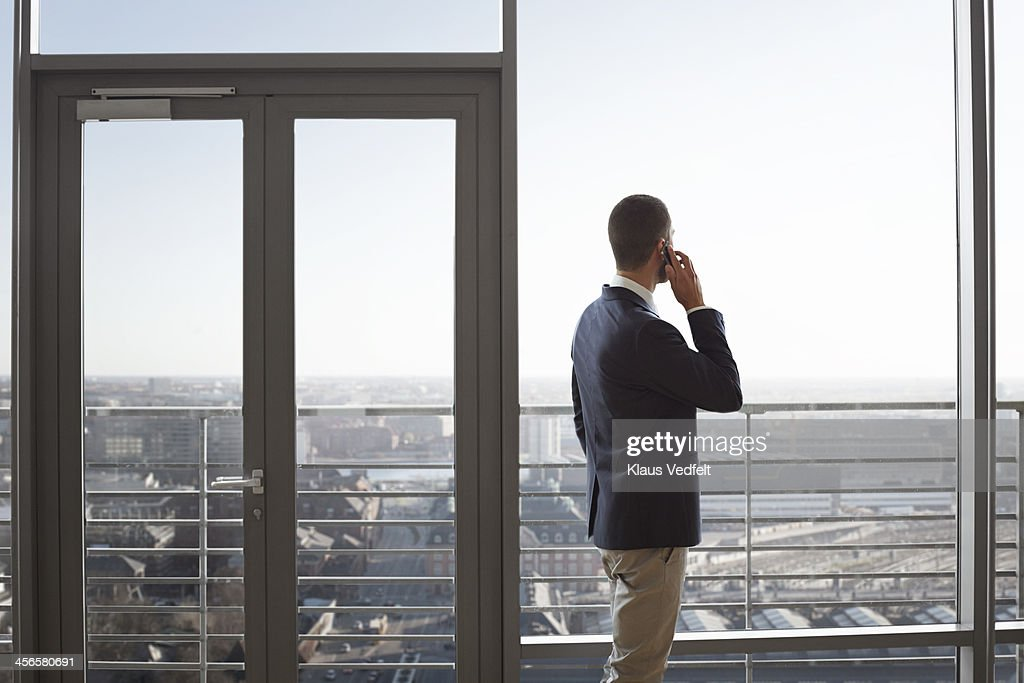 Businessman looking at skyline & holding phone : Stock Photo
