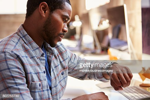 Businessman Looking At Smart Watch In Design Office : Stock Photo