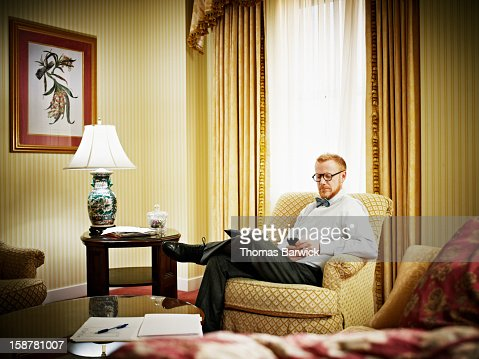 Businessman looking at smartphone in hotel room : Stock Photo