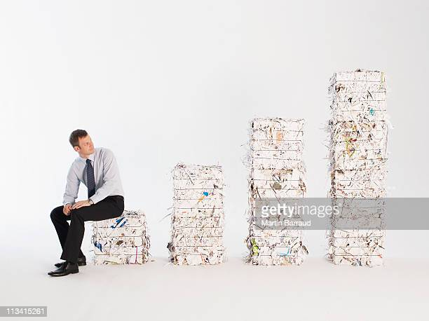Businessman looking at stacks of paper bales