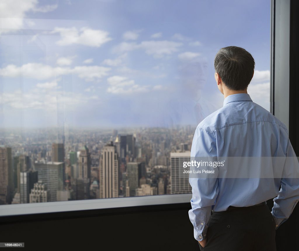 Businessman looking at the window at city : Stock Photo