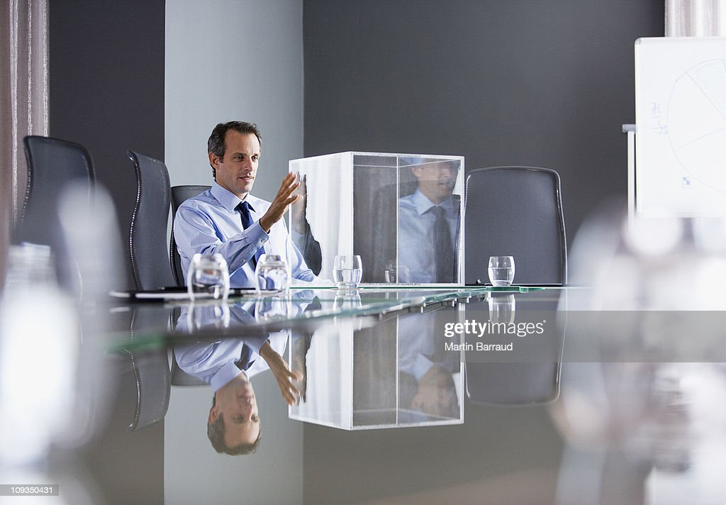 Businessman looking at transparent cube in conference room : Stock Photo