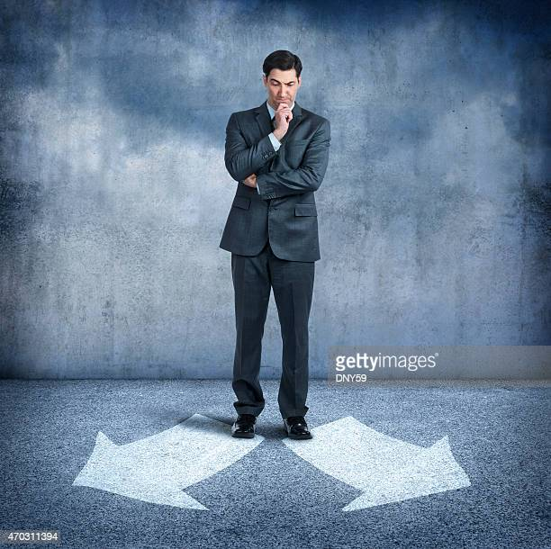 Businessman looking at two arrows pointing in opposite directions
