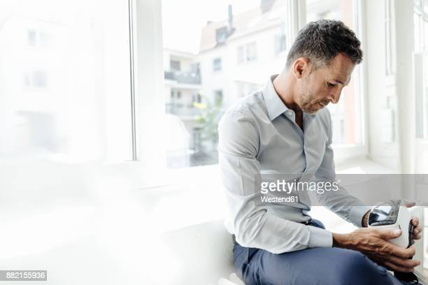 Businessman looking at VR glasses at the window