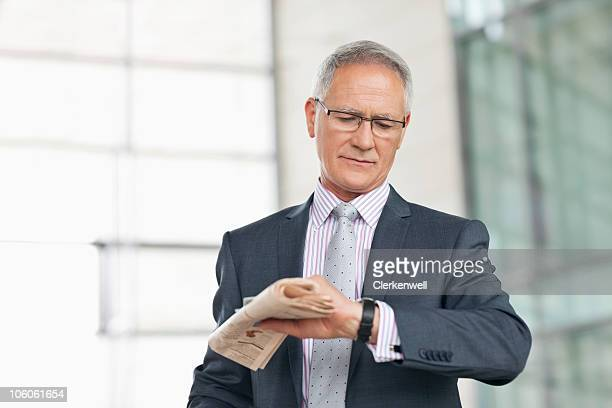 Businessman looking at watch in airport
