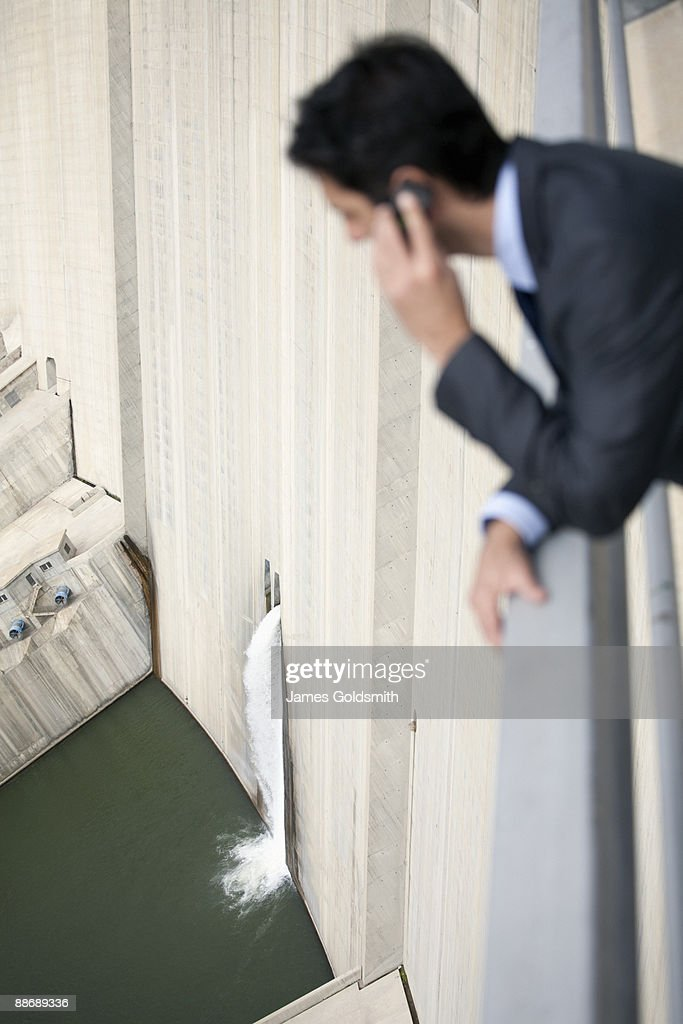 Businessman looking at water spilling from dam : Stock Photo