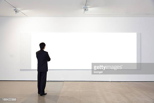 Businessman looking at white frames in an art gallery
