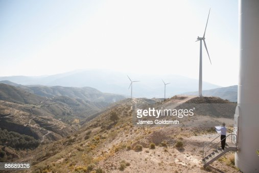 Businessman looking at wind turbines in remote area : Stock Photo