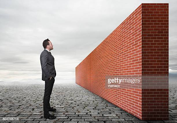 Businessman looking brick wall
