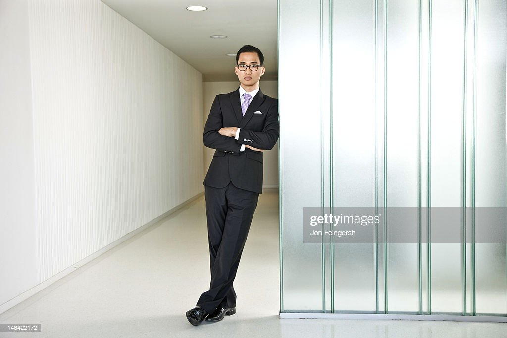 Businessman looking confident leaning on wall : Stock Photo