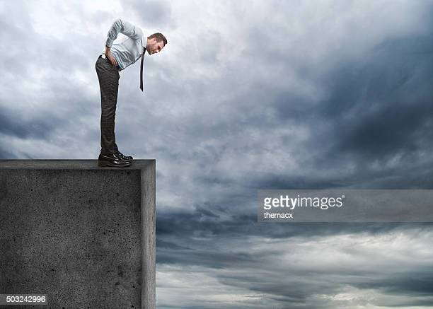 Businessman looking down on cliff