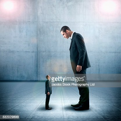 Businessman looking down on miniature colleague