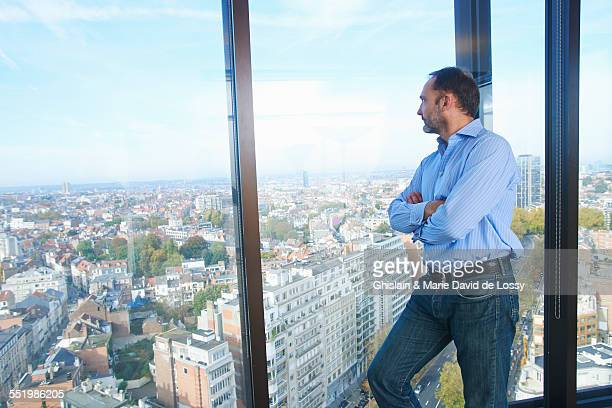 Businessman looking from office window at Brussels cityscape, Belgium