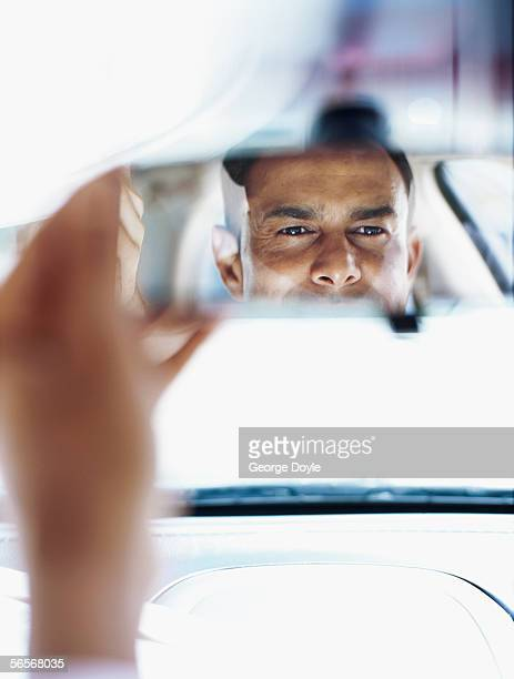 businessman looking in a rear view mirror in a car
