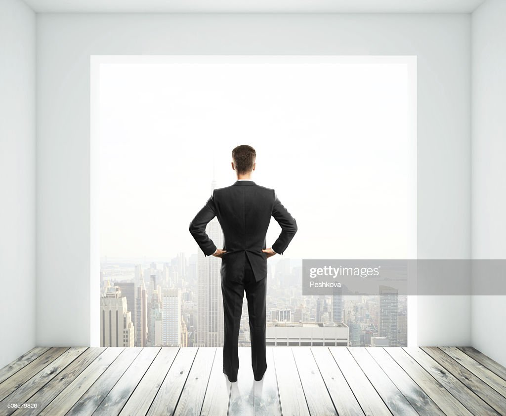 businessman looking in big window : Stock Photo
