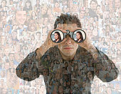 Businessman looking in binoculars over montage of smiling faces