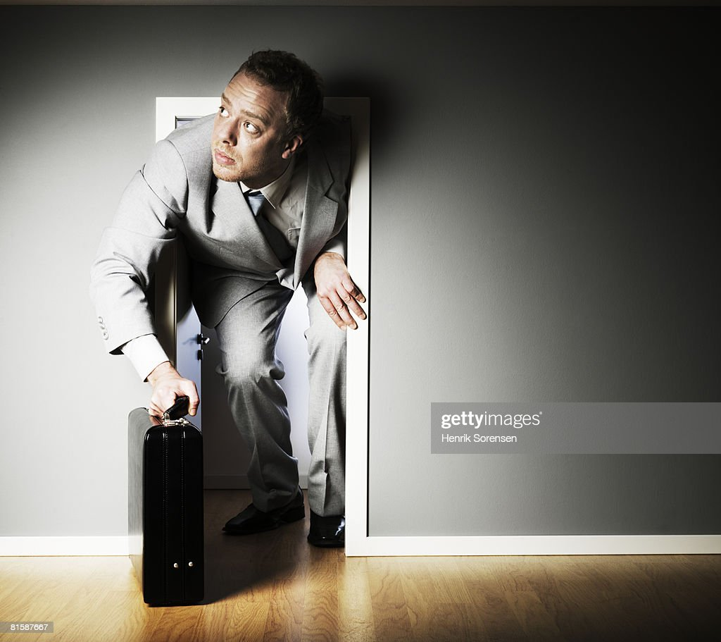 Businessman looking in through a very small door.
