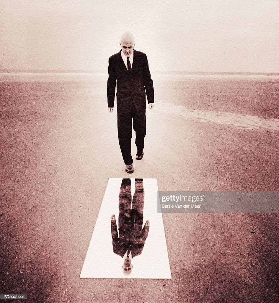 person looking in full length mirror. businessman looking into full length mirror on beach (toned b\u0026w) : stock photo person in o