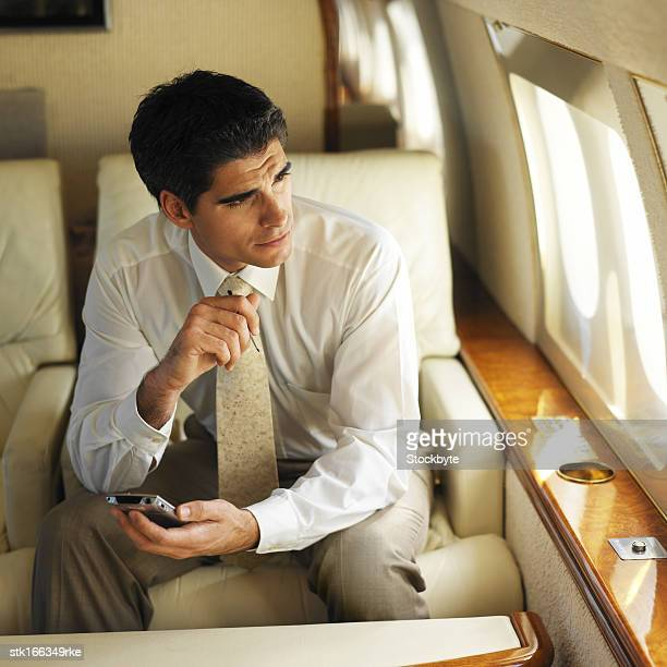 businessman looking out a window in an airplane