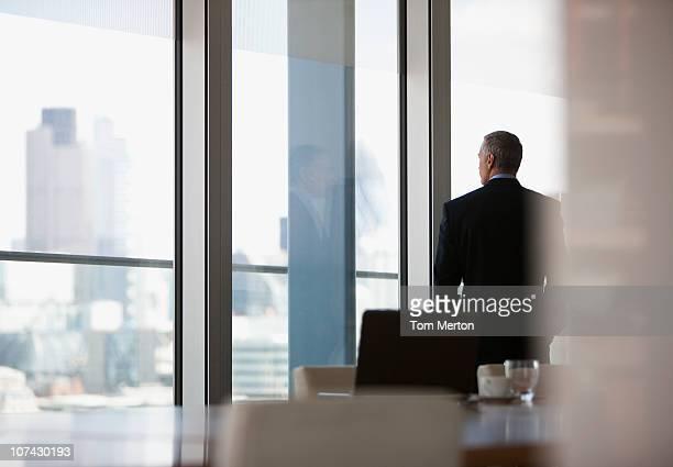 Empresário, olhando para fora da janela de Sala de Conferência