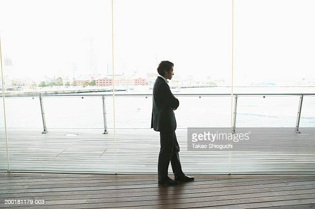 Businessman looking out glass wall, side view