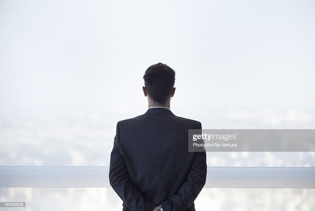 Businessman looking out high rise window at view of city below, rear view