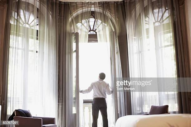 Businessman looking out hotel room window