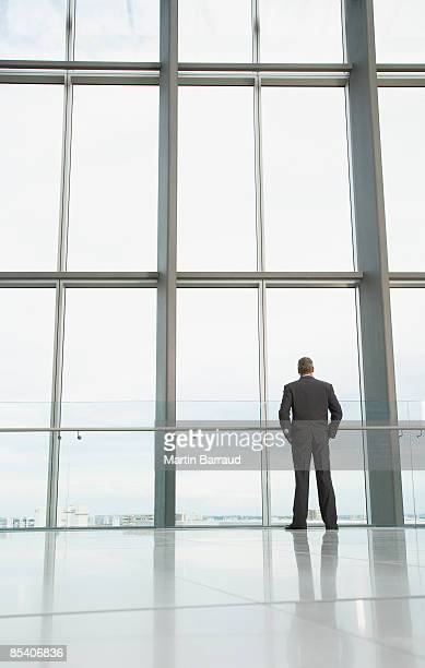 Businessman looking out lobby window