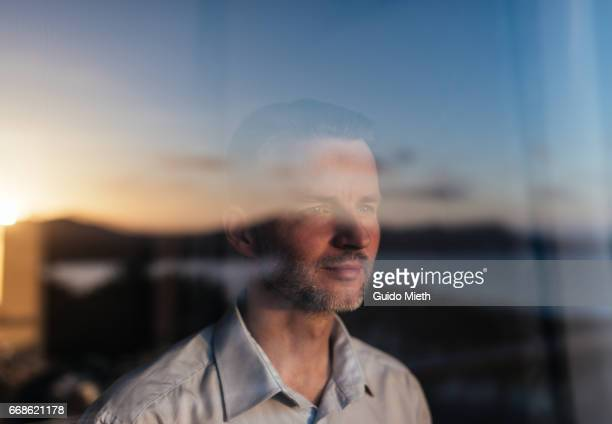 Businessman looking out of a window.