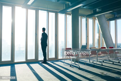 Businessman looking out of office over city : ストックフォト