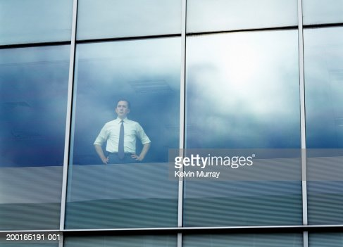 Businessman looking out of office window, low angle view : Foto de stock