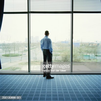 Businessman looking out of office window, rear view : Bildbanksbilder