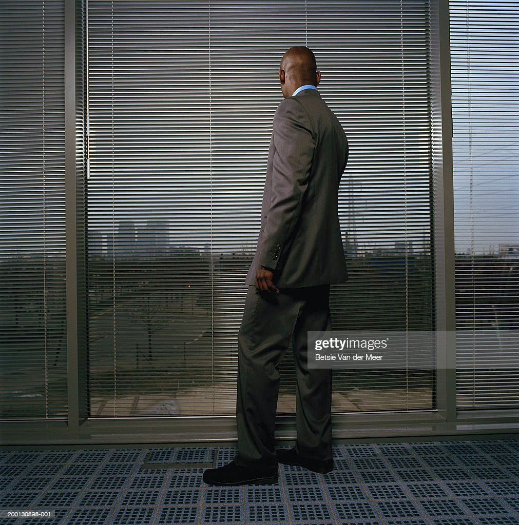 Businessman looking out of office window through blinds, rear view : Stock Photo