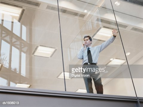 Businessman Looking Out of the Window of an Office Building and Using a Mobile Phone : Stock Photo