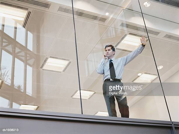 Businessman Looking Out of the Window of an Office Building and Using a Mobile Phone