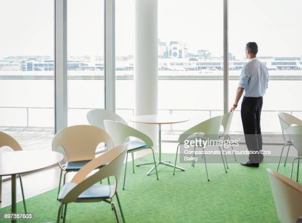 Businessman looking out of window in cafe