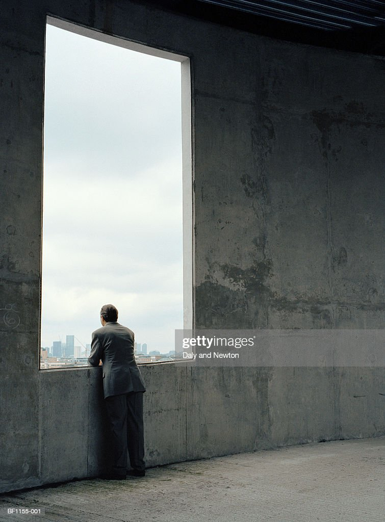 Businessman looking out of window in concrete wall, rear view : Stock Photo