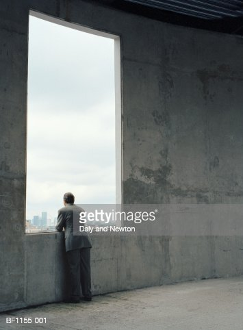 Businessman looking out of window in concrete wall, rear view : Stock-Foto