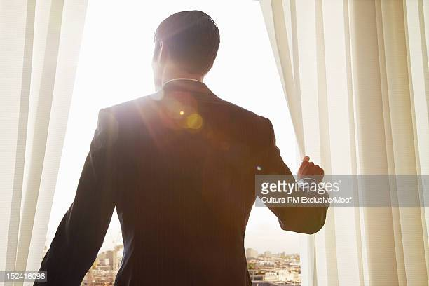 Businessman looking out office window