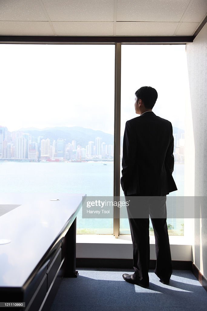Businessman looking out office window, rear view : Stock Photo