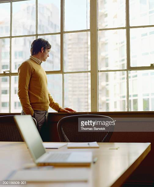 Businessman looking out office window, side view