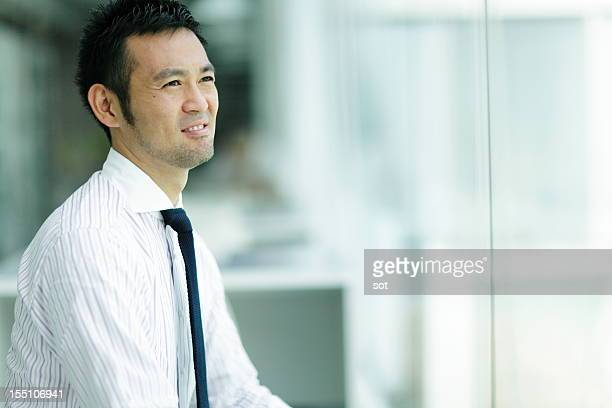 Businessman looking out office window,close up