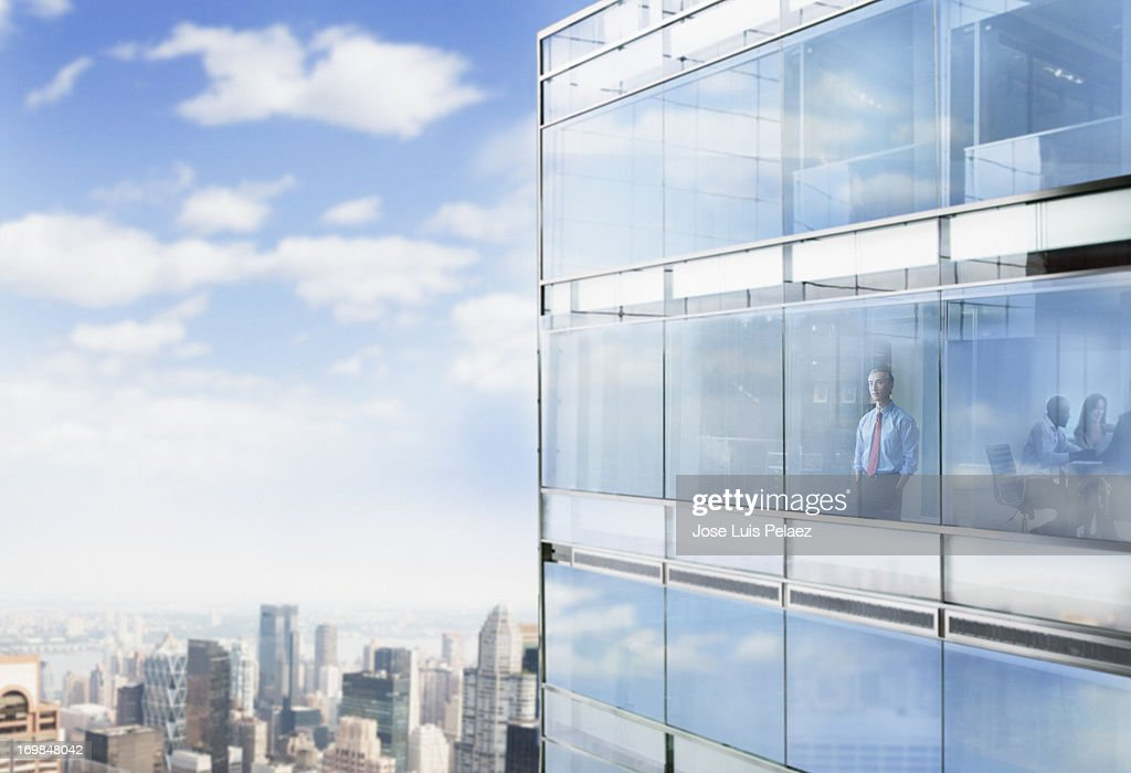 Businessman looking out the window at city : Stock Photo