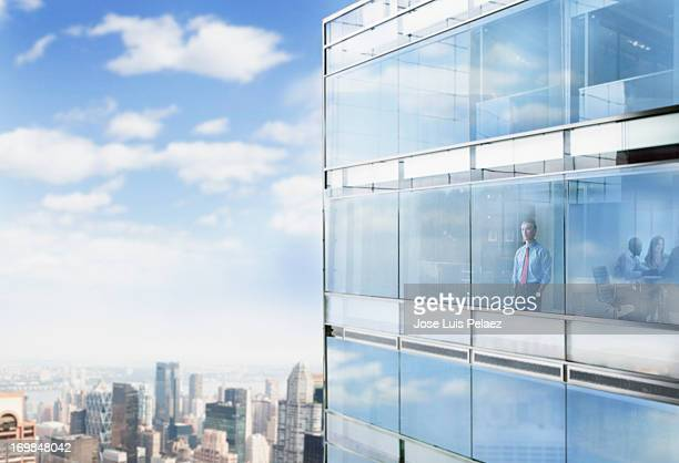 Businessman looking out the window at city