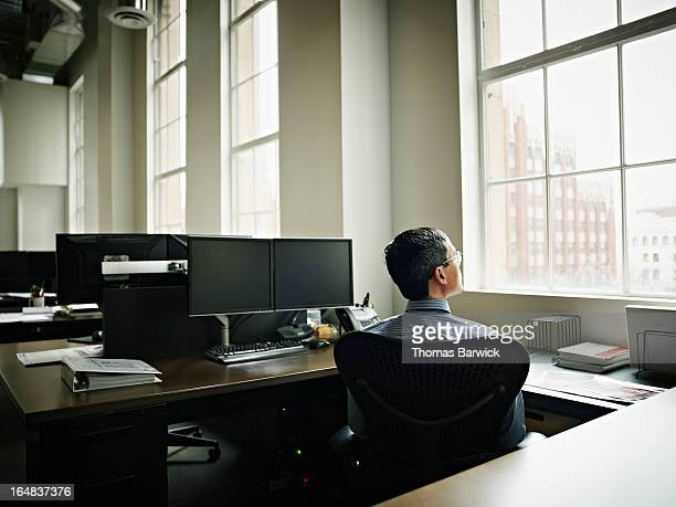 Businessman looking out window at cityscape