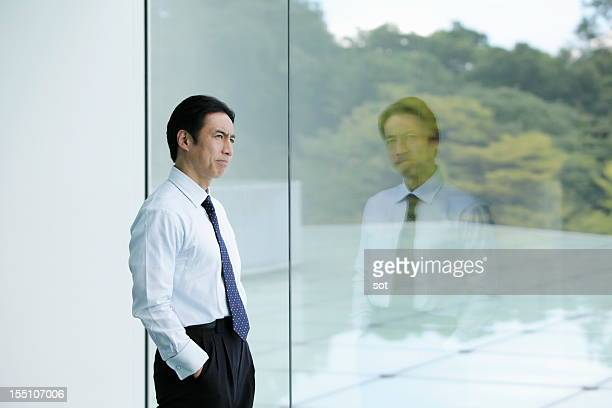 Businessman looking out window in office hallway