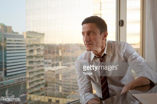 Businessman looking out window to city : Stock Photo