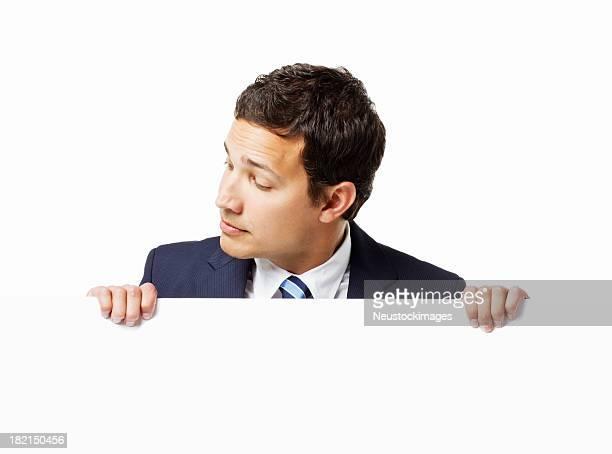 Geschäftsmann schaut über eine Wand. Isoliert